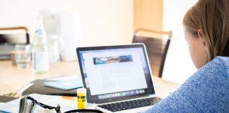Una joven participa en un curso virtual en su computadora. A su lado aparecen útiles escolares.